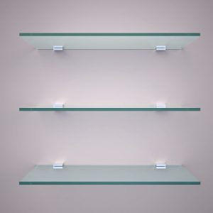 An image of three glass shelves hanging on a plain white wall.