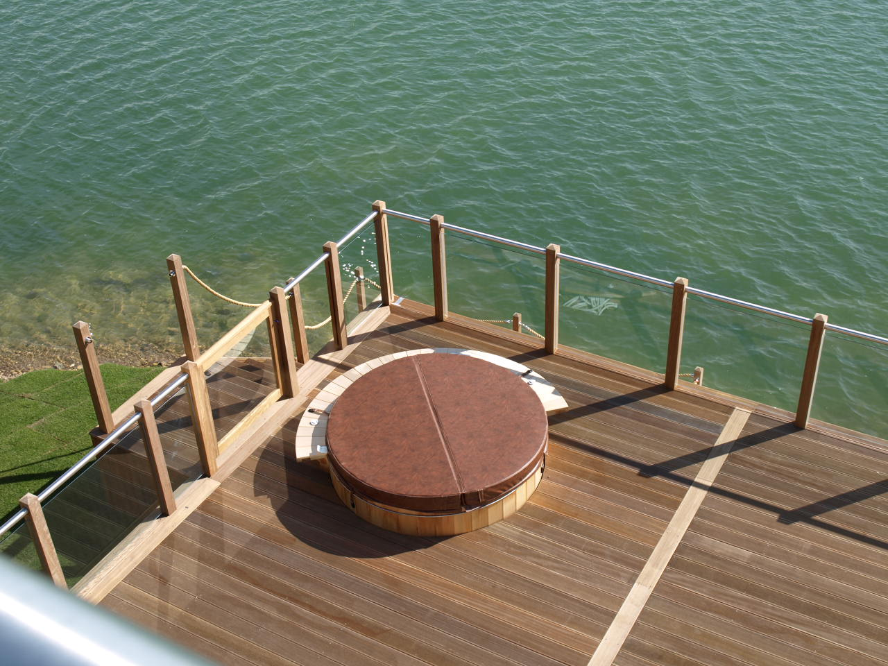 A picture taken from above of wooden decking surrounded by outdoor glass balustrades next to a lake